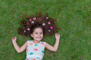 Beautiful and happy girl playing in the park, with wonderful lawn and flowers